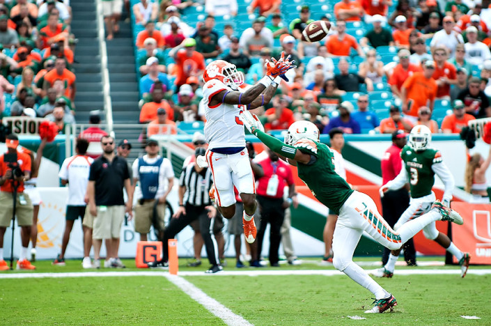 Clemson WR #3, Artavis Scott, goes up for a pass with Miami Hurricanes safety #2, Deon Bush defending