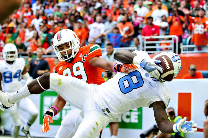 Hurricanes DB, Corn Elder tries to knock the ball away from RB, T.J. Logan of the Tar Heels