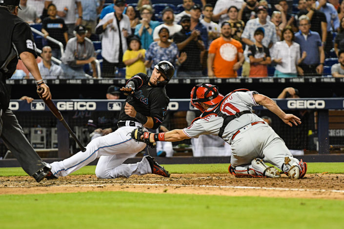 Miami Marlins shortstop Miguel Rojas (19) slides past the tag of Philadelphia Phillies catcher J.T. Realmuto (10)